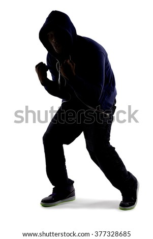 Silhouette of a man in a fighter stance practicing martial arts by shadow boxing.  The man is anonymous because he is backlit and isolated on a white background.