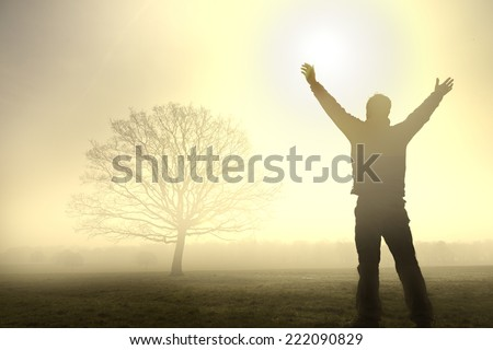 Silhouette of a man in a misty field, raising his hands in joy. - stock photo