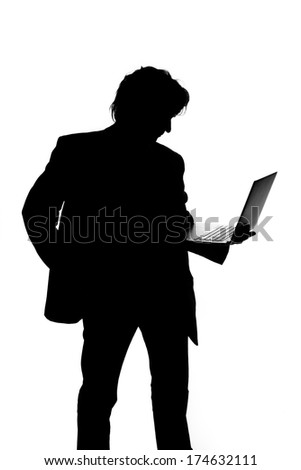 Silhouette of a man in suit holding laptop - stock photo