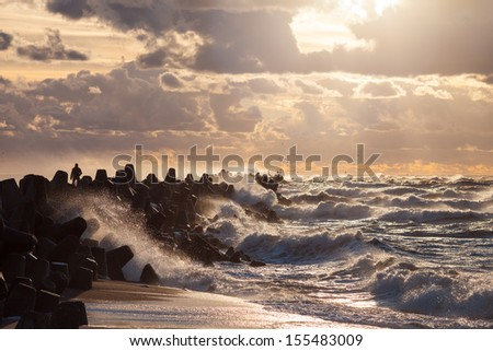 Silhouette of a man is facing storm standing on water breaker with waves and water splashes on Baltic sea while sunset - stock photo