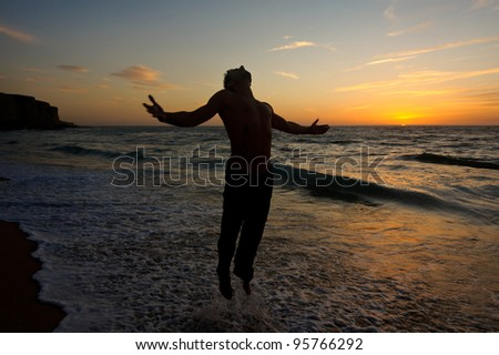 silhouette of a man jumping at sunset at the beach beautiful seascape - stock photo