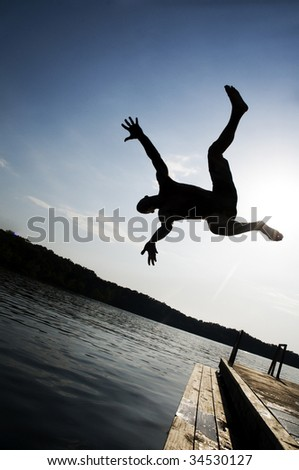 Silhouette of a man jumping into a lake with arms out - stock photo