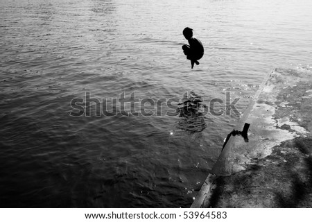Silhouette of a man jumping into the sea - stock photo