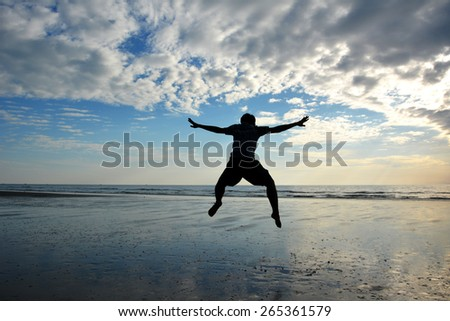 Silhouette of a man jumping on the beach