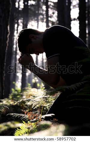 Silhouette of a man kneeling and praying in the forest - stock photo