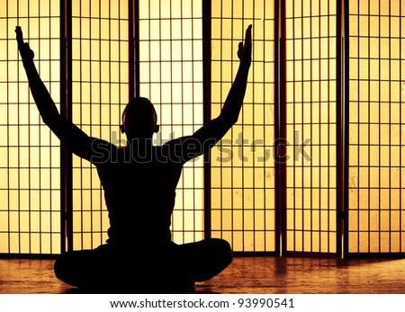 Silhouette of a man meditating and finding a zen moment - stock photo