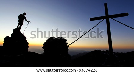 Silhouette of a man on a mountain summit at dawn - stock photo
