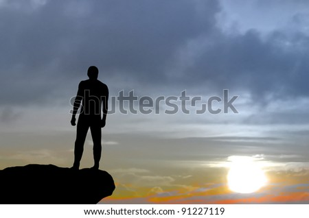 silhouette of a man on a mountain top fixed his gaze into the distance. natural composition
