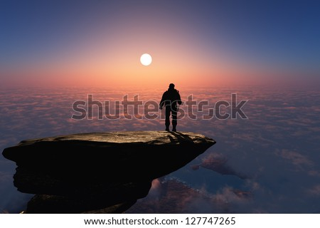Silhouette of a man on a rock. - stock photo