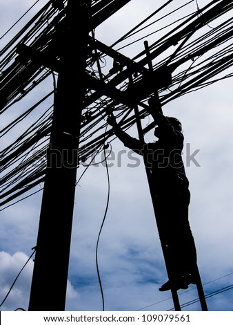 Silhouette of a man on ladder fixing electricity post - stock photo