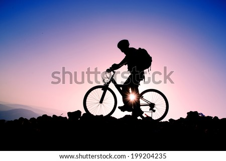 Silhouette of a man on mountain bike at sunset - stock photo