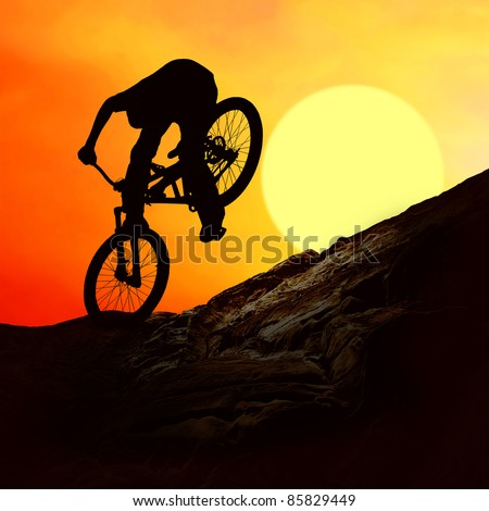 Silhouette of a man on mountain-bike, sunset - stock photo