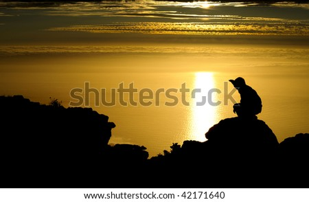 Silhouette of a man on top of a mountain at sunset - stock photo
