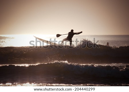 Silhouette of a man paddle boarding with filter effects applied. - stock photo