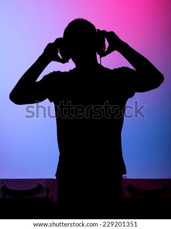 Silhouette of a man. Portrait of a young man with earphones on the colored background. - stock photo