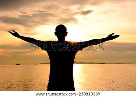 Silhouette of a man raising his arms on sea water & twilight sky background - happy, relax & success concept