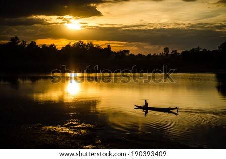 Silhouette of a man rowing in the canoe. - stock photo