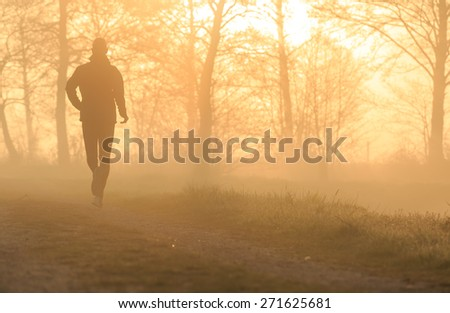 Silhouette of a man running during a foggy, spring sunrise in the Dutch countryside. - stock photo