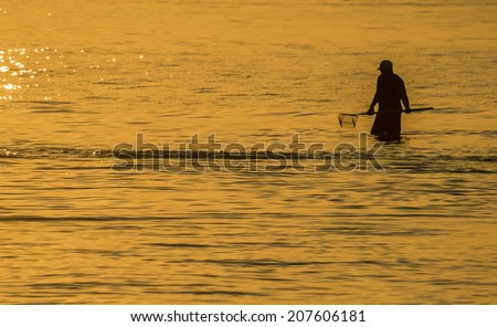 Silhouette of a man searching for clams at sunset in the water of the Indian River Inlet (Delaware). - stock photo