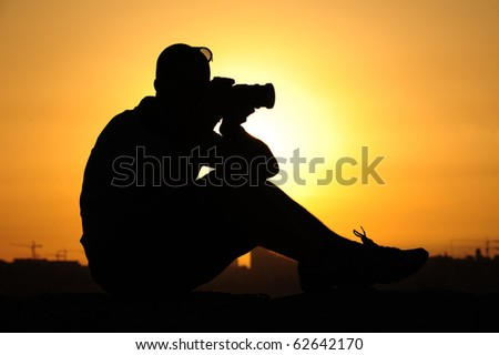 silhouette of a man sitting and taking a photo - stock photo