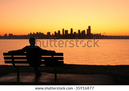 silhouette of a man sitting on a park bench watching the sun rise behind Seattle skyline - stock photo