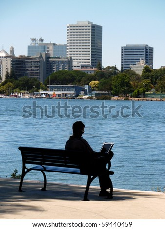 Silhouette of a man sitting on bench by Lake Merritt using laptop - stock photo