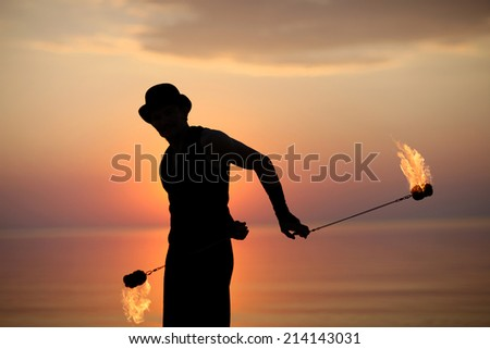 Silhouette of a man spinning fire poi  - stock photo