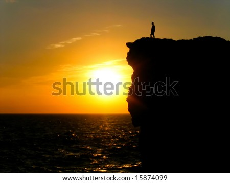 Silhouette of a man standing on an Atlantic Ocean cliff watching the sunrise. - stock photo