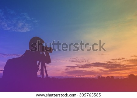 Silhouette of a man taking a photo of sunset in vintage tone - stock photo