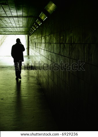 silhouette of a man talking on a cell phone under a walking passage