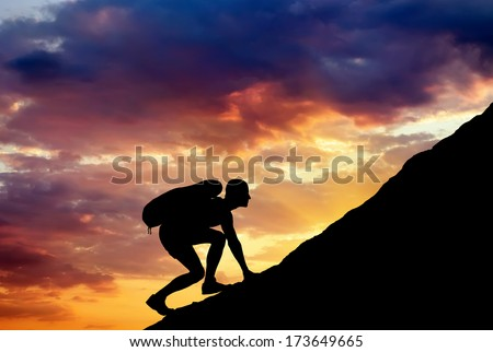Silhouette of a man that climbs the mountain on sunset sky background. Climbing a mountain.  - stock photo
