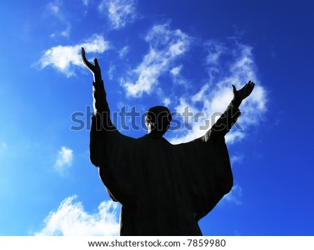 Silhouette of a man that praying with the arms direct to the sky - stock photo