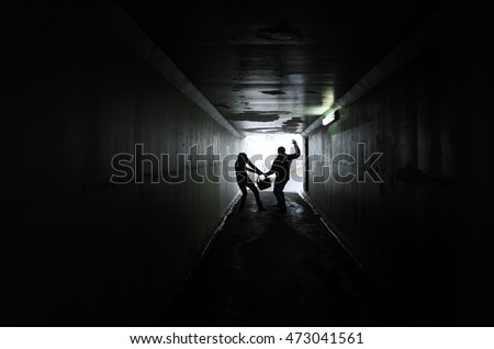 Silhouette of a man thief steals a bag from a woman in a dark tunnel. Violence against women concept. Real people, copy space