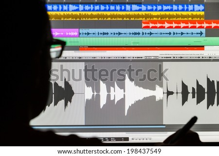Silhouette of a man using a Digital Audio Workstation to edit sound and arrange music - stock photo