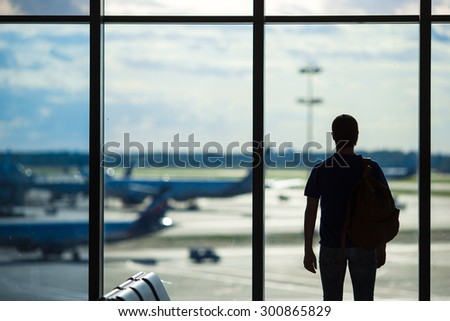Silhouette of a man waiting to board a flight in airport - stock photo