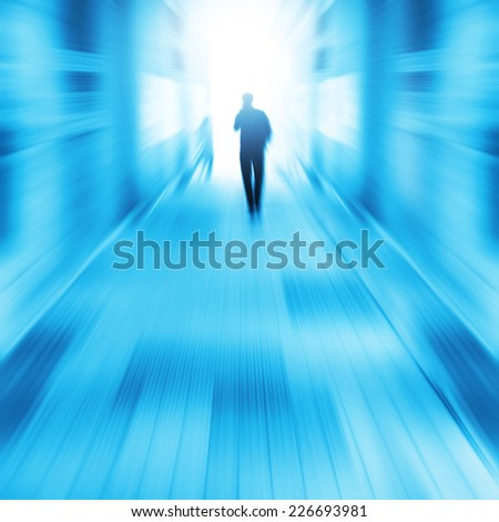 Silhouette of a man walking in a tunnel to light. - stock photo