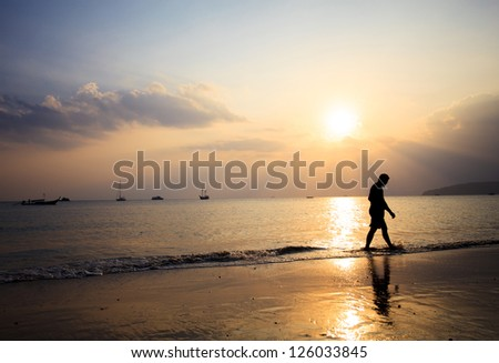 silhouette of a man walking on the beach