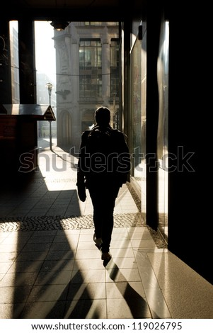 Silhouette of a man walking on the street - stock photo
