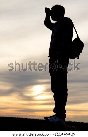 Silhouette of a man with a satchel on his back standing with his hand raised to his forehead looking into distance against a delicate sunset - stock photo