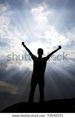 Silhouette of a man with arms stretched out to the sky - stock photo