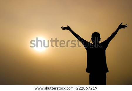 Silhouette of a man with arms up in morning.