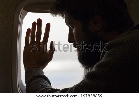 Silhouette of a man with beard flying in airplane - stock photo