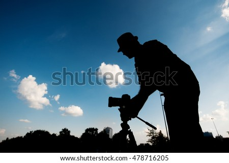 silhouette of a man with camera on the sky background