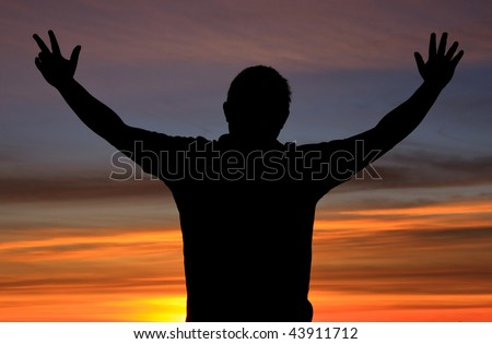 Silhouette of a man with freedom action during sunrise