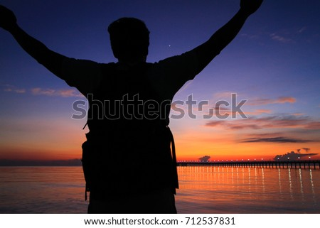 Silhouette of a man with hands raised in the beautiful sunrise.