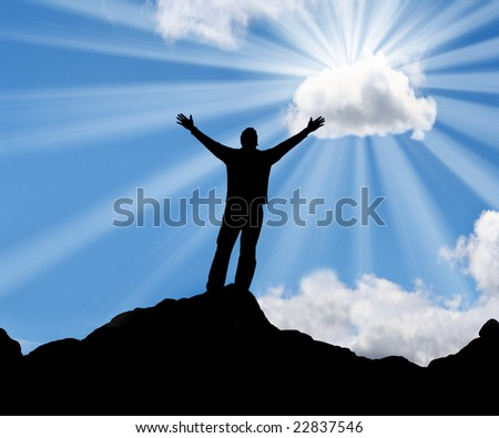 Silhouette of a man with his arms stretched out to the sun. - stock photo