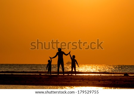 Silhouette of a man with his children on the beach at sunset.