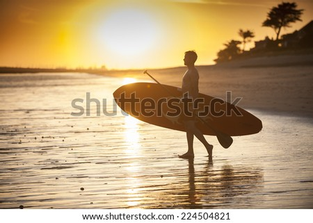 silhouette of a man with his paddle board on the beach at sunset - stock photo