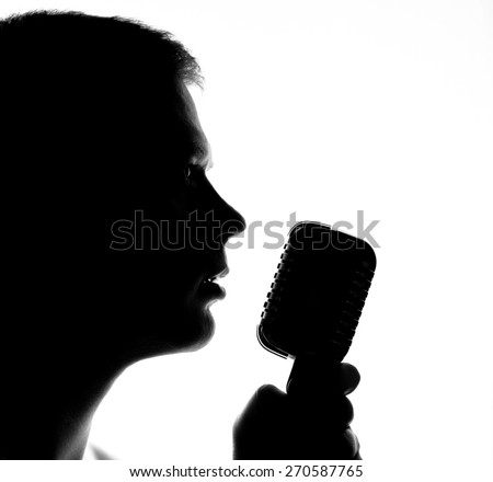 Silhouette of a man with microphone. - stock photo