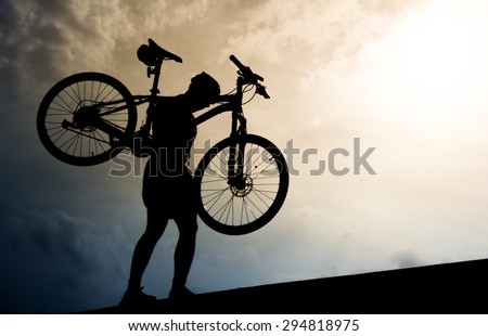 Silhouette of a man with mountain bicycle lifted above him. - stock photo